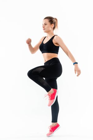 Young sporty blond woman in a black sportswear jumping isolated over white background. Sport activity Reklamní fotografie