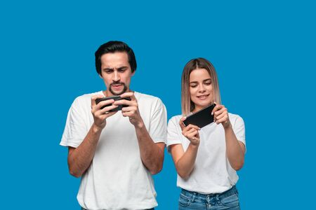 Beautiful couple wearing white t-shirts standing isolated over blue background, playing games on mobile phone