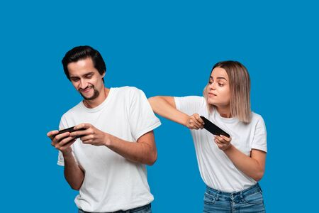 Beautiful couple wearing white t-shirts standing isolated over blue background, playing games on mobile phone.