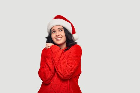 Beautiful brunette girl in a red sweater and Santa Claus hat dreaming about the best gift for Christmas and New Year.