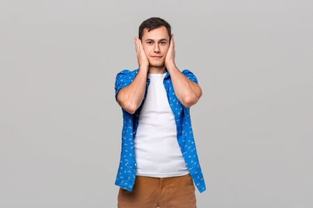 Young man covering ears with hands. Gesture of three wise monkeys. Do not hear