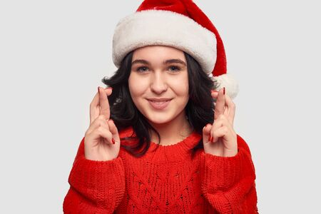 Beautiful brunette girl in a red sweater and Santa Claus hat holding fingers crossed dreaming about the best gift for Christmas and New Year.