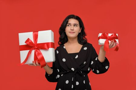 Smiling brunette woman in a black dress choosing between small and big Christmas giftboxes with red ribbon. Hurry up to buy gifts for Christmas and New Year