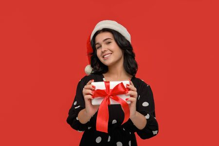 Pretty brunette woman in a black dress and Santa hat smiling holding Christmas giftbox of white color with red ribbon. Hurry up to buy gifts for Christmas and New Year
