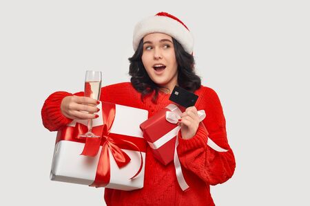 Brunette girl in a red sweater and Santa hat holding giftboxes with red ribbon for Christmas and New Year, bank card after shopping and glass of champagne. Buy gifts for Christmas and New Year