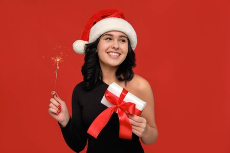 Excited girl in a black dress and Santa hat holding Bengal lights and gif box celebrating Christmas and New Year. Having a good time at Christmas party. Stock Photo