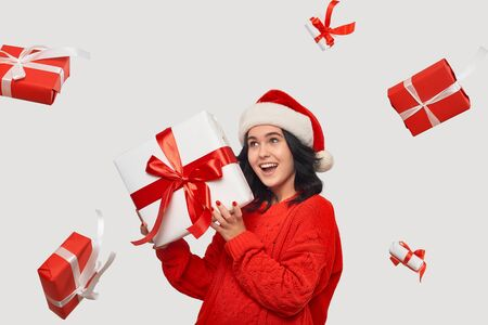 Brunette girl in a red sweater and Santa Claus hat holding white giftbox with red ribbon for Christmas and New Year. Several gift boxes flying around the model. Magic of Christmas