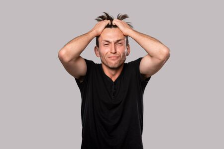 Man facing serious problem isolated over grey background. Concept of emotional stress