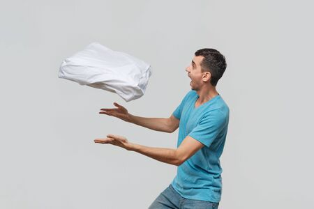 Pretty brunet man in a blue tee shwoing magic making the pillow to levitate. Time to go to sleep and take a rest.