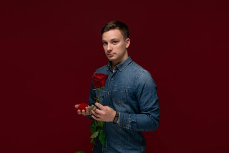 Young man making wedding proposal holding one red rose and box with engagement ring. Concept of love.