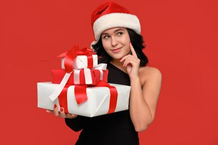 Pretty brunette woman in a black dress and Santa hat is smiling holding several Christmas giftboxes of different sizes of white color with red ribbon. Hurry up to buy gifts for Christmas and New Year