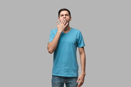 Young brunet man yawning isolated over grey background. Being tired after long working day. Concept of sleeping.