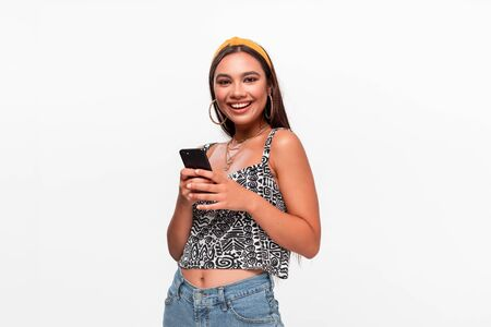 Pretty african-american teenager in a headband, sleeveless t-shirt and jeans smiling holding smartphone.