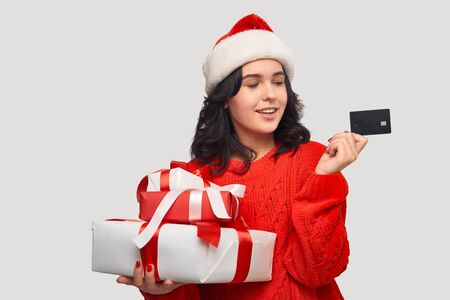 Beautiful brunette girl in a red sweater and Santa hat holding giftboxes with red ribbon for Christmas and New Year and bank card after shopping. Buy gifts for Christmas and New Year