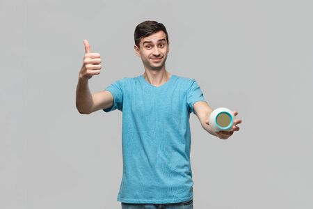 Young brunet man showing thumb up holding alarm isolated over grey background. Concept of being in time. Hurry up