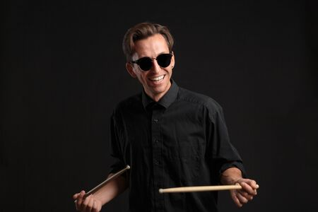 Stylish man drummer in a black shirt and sun glasses playing drums with sticks over dark background. Jazz musician on a stage