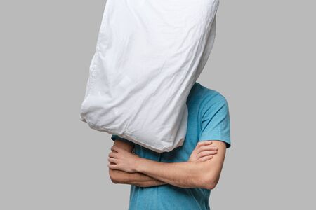 Flying white pillow hitting pretty brunet man in a blue tee. Time to go to sleep and take a rest. Banque d'images