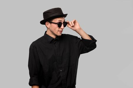 Portrait of a stylish handsome man in a black shirt, pork pie and sun glasses hat isolated over grey background. Banque d'images