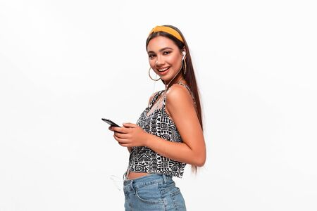 Pretty african-american teenager in a headband, sleeveless t-shirt and jeans smiling looking at the screen of a smartphone.