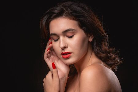 Beautiful woman with bright makeup posing isolated over black background. Image of young beautiful woman with red lips Imagens