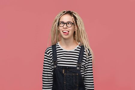 Teenager with dreadlocks in a striped shirt and jeans jumpsuit shwoing grimace isolated over pink background. Being funny and crazy