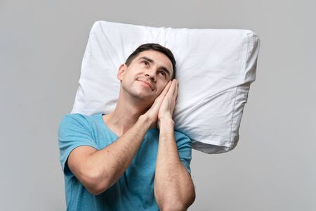 Tired brunet man in a blue tee resting on a white pillow isolated over grey background. Resting after long day.