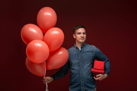 Handsome man with coral balloons and red giftboxes isolated over dark red background. Romantic mood Stock Photo - 137471113