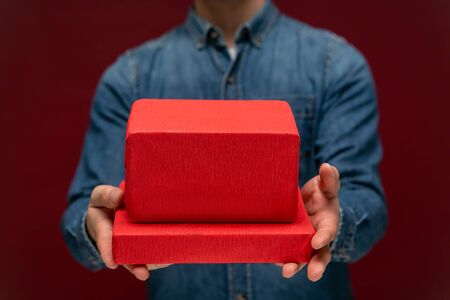 Young man holding red giftbox isolated over red background. Concept of love