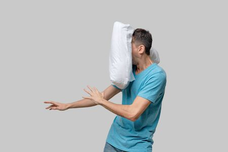 Flying white pillow hitting pretty brunet man in a blue tee. Time to go to sleep and take a rest.