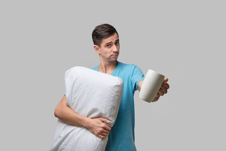 Young brunet man holding white cup of coffee and white pillow. Waking up in the morning.