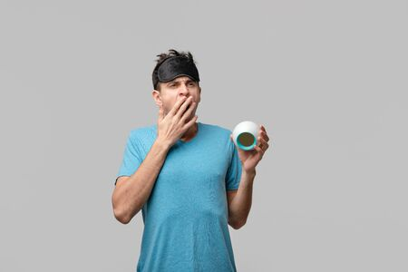 Young brunet man with black sleep mask on a head yawning holding alarm-clock isolated over grey background. Time to wake up Stock Photo