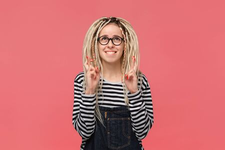 Portrait of a young girl with long dreads standing over pink background holding fingers crossed for good luck