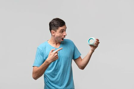 Young brunet man is shocked holding alarm-clock isolated over grey background. Time to wake up