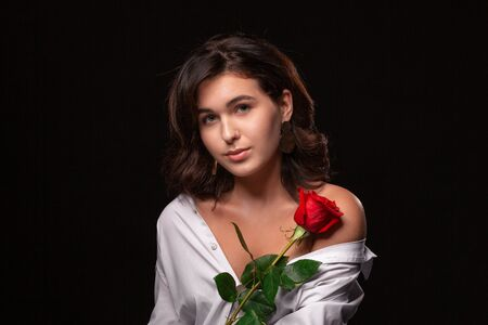 Beautiful woman with bright makeup posing isolated over black background with red rose. Image of young beautiful woman with red lips in a white shirt