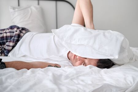Young man in the white shirt smiling lying on a bed with white linen and covers his head with a pollow. Concept of relaxation Stock Photo