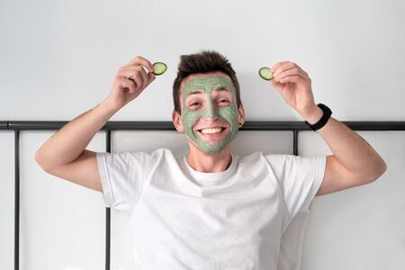 Young man in a white shirt with applied green cosmetic mask is happy holding pieces of cucumber. Concept of wellbeing and facial treatment for men Stock Photo