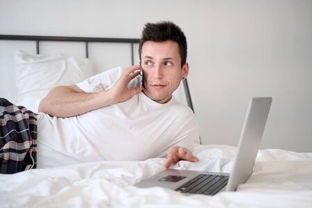 Young man in the white shirt and pajama sitting on a bed looking at the screen holding bank card. Online shopping Stock Photo