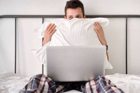 Frightened handsome young man in the white shirt and pajama sitting on a bed with laptop hding behind pillow. Morning of a freelancer