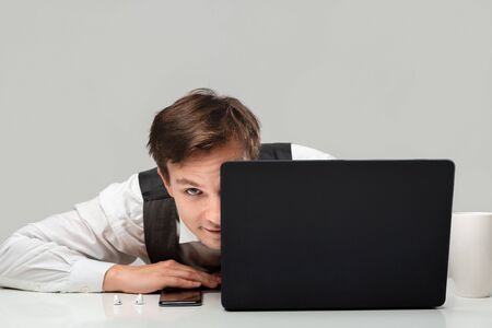 Businessman in a white t-shirt and grey vest is hiding behind laptop. Having problems. Daily business routine. Stock Photo