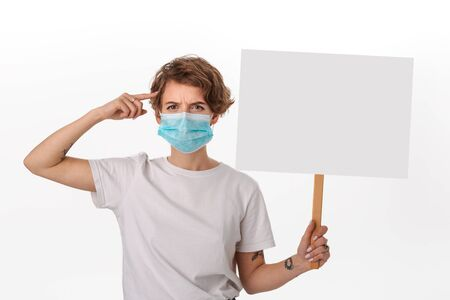 Worried young woman in a white shirt wearing blue medical mask holds picket sign with copy space and piniting at her head. Think about protection from coronavirus.