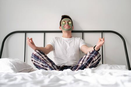 Young man in a white shirt with applied green cosmetic mask and pieces of cucumber on eyes is relaxing on a bed with white bed linen. Concept of wellbeing and facial treatment for men Stock Photo