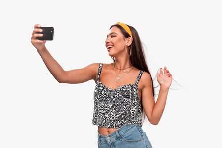 Pretty african-american teenager in a headband, sleeveless t-shirt and jeans smiling making selfie with a smartphone. Mobile Photography
