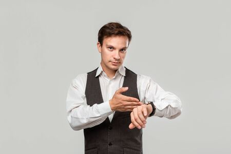 Young businessman in a white shirt and grey vest pointing at the hand watch to highlight that tie has come. Concept of time