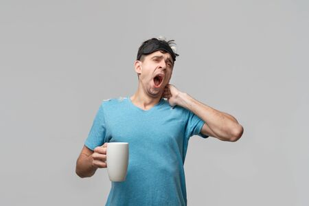 Young brunet man with sleep mask holding white cup with coffee isolated over grey background. Time to wake up