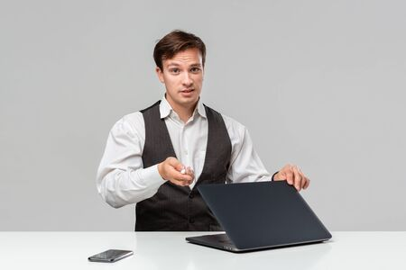 Businessman in a white t-shirt and grey vest working on a laptop. Man looking at the camera. Daily business routine.