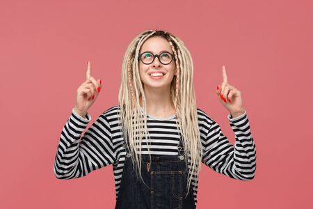 Smiling young girl with dreadlocks in a striped shirt and jeans jumpsuit pointing with two fingers at copy space up. Place for advertising