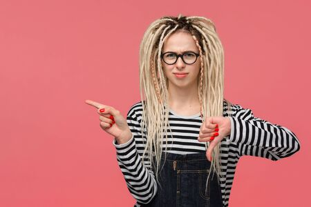 Beautiful young girl with dreadlocks in a striped shirt and jeans jumpsuit is upset holding thumb down and pointing with finger at copy space. Concept of dislike