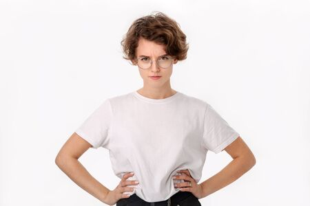Gloomy young woman in white shirt and eyeglasses with arms akimbo looking at the camera. Concept of dislike Stock Photo