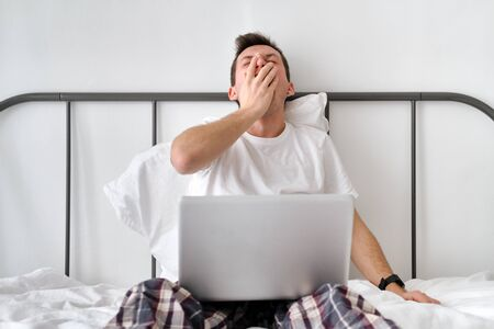 Smiling handsome young man in a white shirt and pajama sitting on a bed with laptop and stretching. Morning of a freelancer Stock Photo