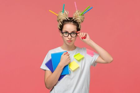 Smiling student in a white shirt and glasses, sticky notes on a shirt and colorful markers in dreads holding two notebooks. Education is tough